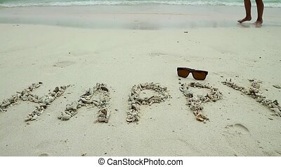 Inscription happy on sand and seascape on a background.