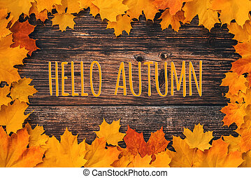 inscription Hello Autumn on a wooden background with a frame of orange maple leaves