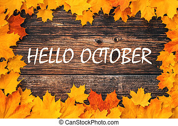 inscription Hello October on a wooden background with a frame of orange maple leaves