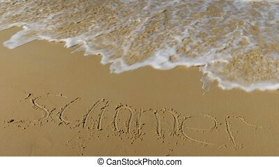 inscription in the sand. Sea wave erases the word summer