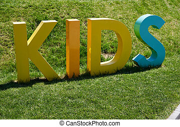Inscription KIDS made in 3D form standing on green grass