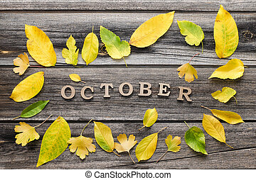 Inscription October on a wooden background, frame of yellow leaves