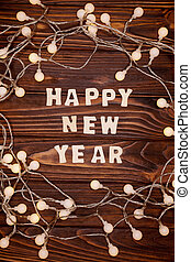 Inscription of Happy New Year on the dark rustic wooden background