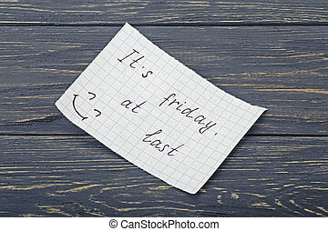 "Inscription on paper ""it's friday at last"" on a wooden board"