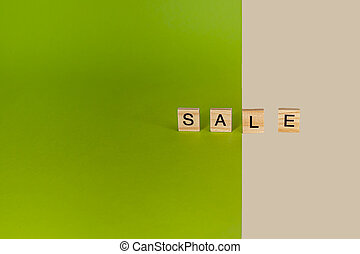 Inscription sale from wooden cubes on colored, yellow and ...