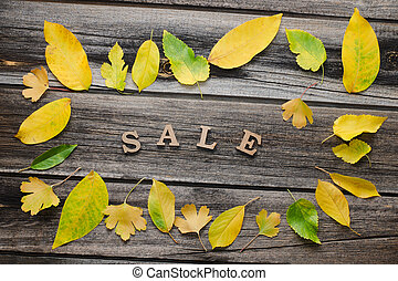 Inscription Sale on a wooden background, frame of yellow leaves
