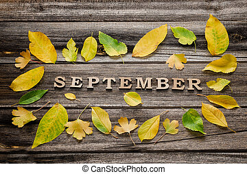 Inscription September on a wooden background, frame of yellow leaves