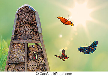 Insect hotel with flying butterflies and shining sun