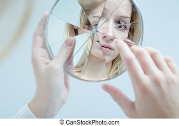 Insecure pretty young woman holding broken mirror