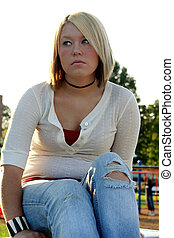 Serious young blond woman sitting outdoors, her eyes averted to the right. Taken from a low perspective.