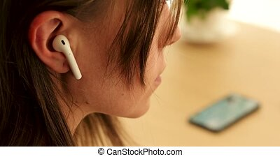 Woman inserts a wireless white earphone into her ear close-up