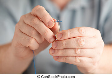 Insert the thread in needle by man hand