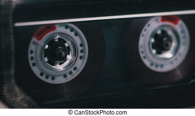 Insert Transparent Audio Cassette into Tape Recorder, Playing and Rotates. Close-up. Vintage audio cassette rotates in tape. Sound recording in retro cassette player. Call recording. Macro. 4K, 10 bit