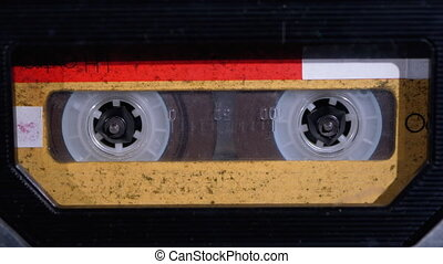 Insert Yellow Audio Cassette in the Tape Recorder, Playing and Rotates. Close-up. Vintage audio cassette tape with a blank label used for sound recording in a retro cassette player. Call recording. Macro
