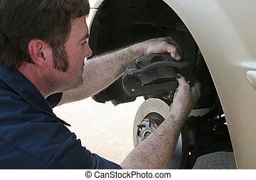 Inserting Brake Pads - An auto mechanic working on disc...
