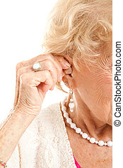 Inserting Hearing Aid - Closeup of a senior woman's hand...