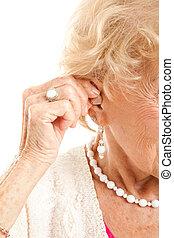 Inserting Hearing Aid - Closeup of a senior woman's hand...