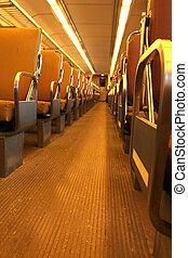 Inside an empty passenger train, rows of seats