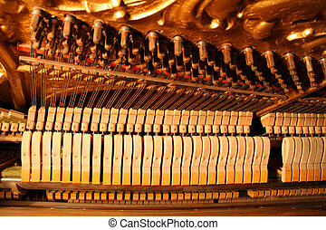 Inside an Upright Piano - Felt Hammers used to strike Steel Strings and wound knobs to tune.