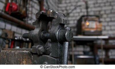 Inside forge workshop - steel vise, slider shot, close up