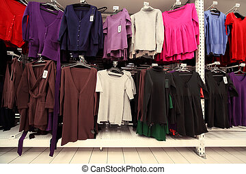 Inside  large women clothing store, multi-colored jerseys sweatshirts