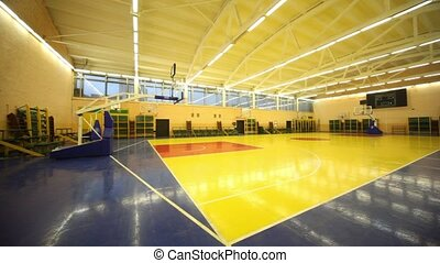 Inside lighted blue yellow school gym hall with basket, view...
