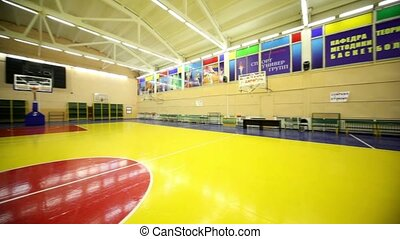 Inside lighted school gym hall with basket