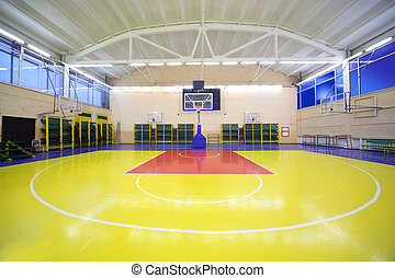 Inside lighted school gym hall with red-yellow floor and...