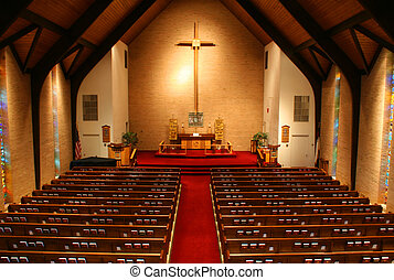 Inside of a large, modern church. View is from the balcony of the church and all the pews and hymnals are visible.