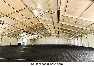 Inside of a huge white tent with rafters