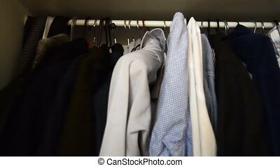 inside of a mans wardroobe, shirts clothes on the hangers.