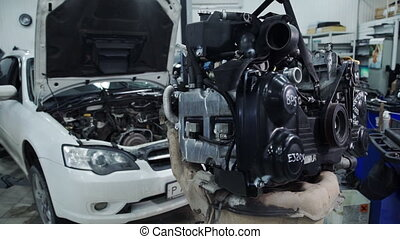 Inside the service autofocus engine hangs in front of a white car.