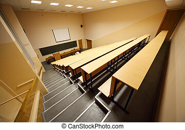 Inside university lecture hall; big blackboard, wooden desks and benches