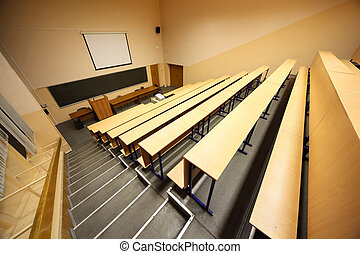 Inside university lecture hall; staircase, wooden desks and...
