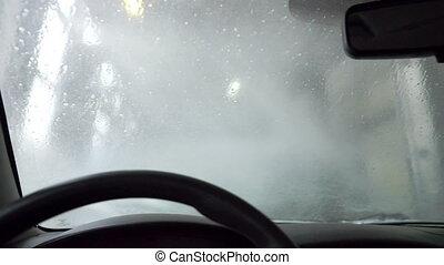 Inside view on windscreen during washing - Water falls down...