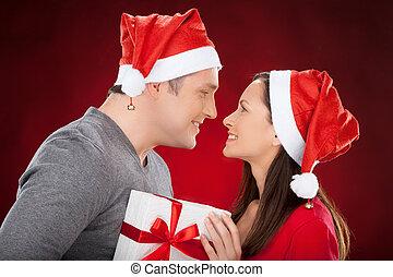 insieme, a, natale, eve., allegro, giovane coppia, in, cappello santa, tenere regalo, scatola, e, sorridente, a, altro, mentre, standing, isolato, su, rosso