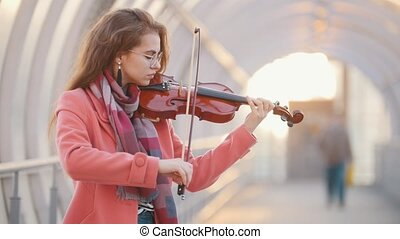 Insipired young woman playing violin on the overhead...