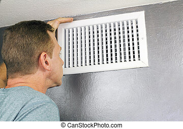 Inspecting a Home Air Vent for Maintenance - Mature man ...