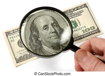 Inspecting a Hundred Dollar Bill - Hundred dollar bill under...