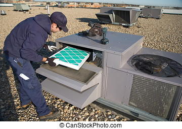 Inspecting roof top unit - Worker changing a roof top air ...