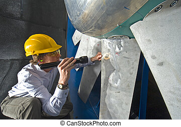 A young engineer inspecting the blades of an industrial windtunnel wearing a hard top, earplugs and protective goggles