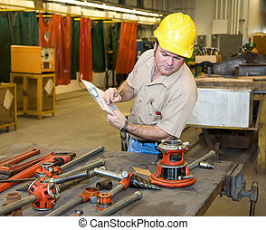 Inspecting Tools - Inspector verifying the condition of...