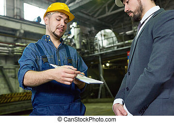 Portrait of young worker wearing hardhat handing clipboard with document to manager for signature