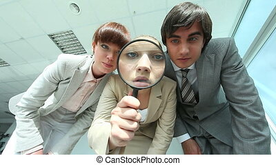 Three office workers inspecting something and pointing at it