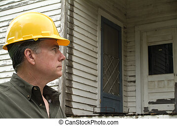 Inspector - A man in a hard hat looking at an old rundown...