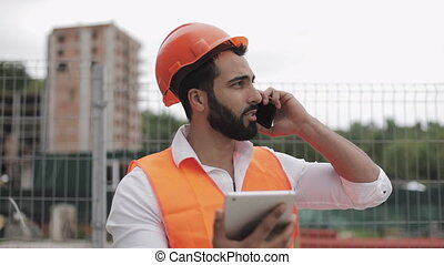 Inspector building supervisor engineer talking on smartphone and working on tablet standing on the construction site background. Profession concept.