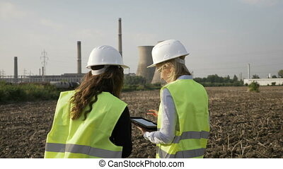 Inspector female engineers examining petroleum refinery...