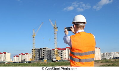 Inspector in a white helmet and an alarm jacket is photographing the construction of an apartment house
