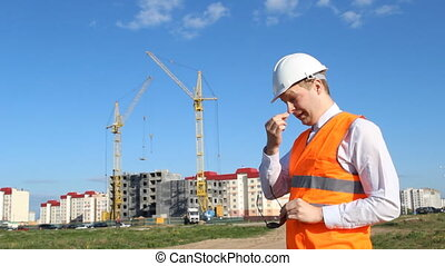 Inspector in a white helmet on the background of building a...