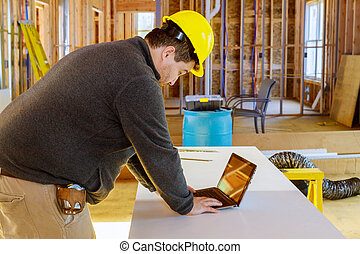 Inspector in new construction house with tablet making notes